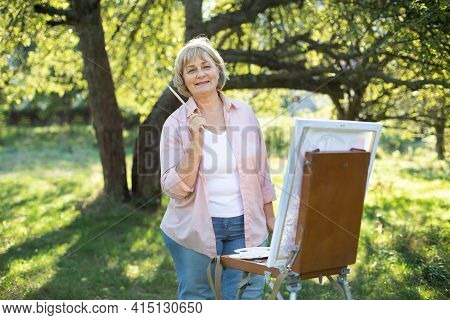 Smiling Beautiful Blond Mature 60-aged Caucasian Woman Artist, Posing To Camera With Brush In Hand,