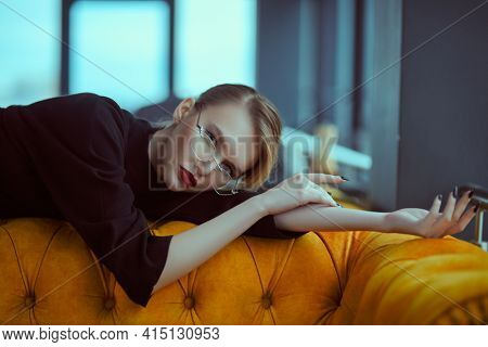 Beautiful girl with elegant romantic appearance in natural light is posing in the interior. Beauty, fashion. Optics and eyewear.