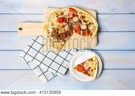 Pizza with bacon, beef forcemeat, onion, cherry tomatoes and mozzarella on wooden table. Top view.