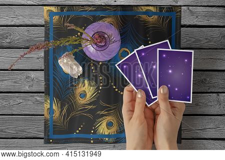 Hands Of Young Woman With Golden Nail Polish Holding Three Tarot Or Oracle Cards, On A Black Peacock