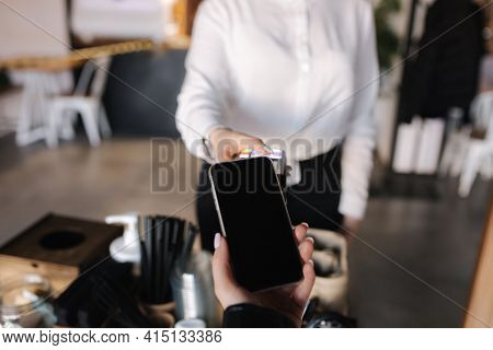 First Person View Of Human Hand Hold Smart Phone For Payment By Nfc At The Cafe. Closeup Of Female H