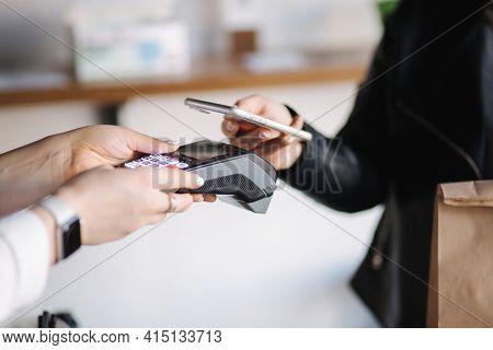 Closeup Of Female Paying With Smartphone During Covid-19 Pandemic. Cashier Hand Holding Credit Card