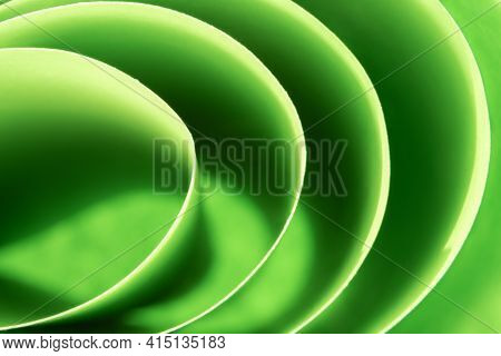 Abstract Colored Macro Background, Created With Curved Green Paper Sheets. Curved Lines And Shapes A