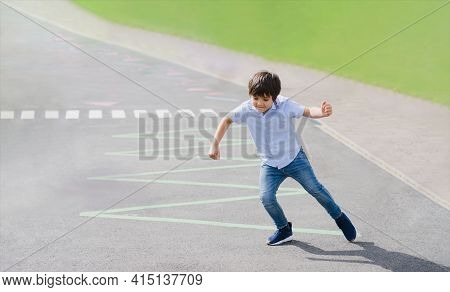 Full Length Portrait Of Young Boy Running Or Jumping On Triangles Line At Asphalt Road, Active Kid P