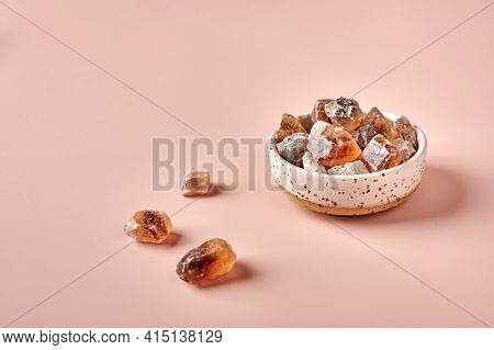 Brown Caramelized Lump Cane Sugar Cubes In A Bowl On Pink Powdered Background, Selective Focus, Copy