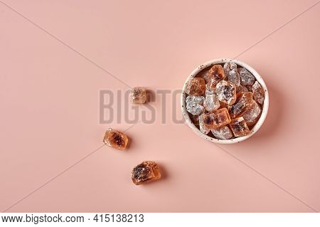 Brown Caramelized Lump Cane Sugar Cubes In A Bowl On Pink Powdered Background, Top View, Copy Space