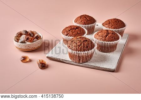 Homemade Chocolate Cupcakes In Baking Paper Forms On Cutting Board On Pink Powdery Background, Selec
