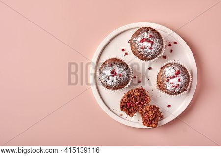 Homemade Chocolate Cupcakes In Baking Paper Forms And Piece Of It On Light Plate On Pink Powdery Bac