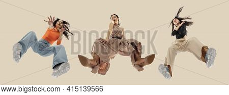 Young Stylish Women In Modern Street Style Outfit Isolated On Brown Background, View From The Bottom