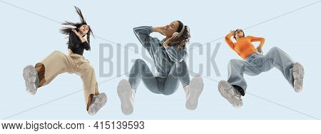 Young Stylish Women In Modern Street Style Outfit Isolated On Blue Background, View From The Bottom.