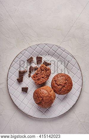 Homemade Chocolate Cupcakes And Pieces Of Chocolate In Textured Plate On Wooden Light Background, Ve