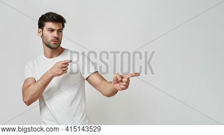 Handsome Young Bearded Man Wearing T-shirt Pointing Fingers To The Side, Picking, Making His Choice