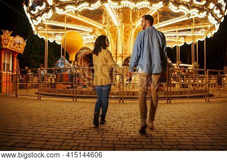 Love couple at the carousel, night amusement park