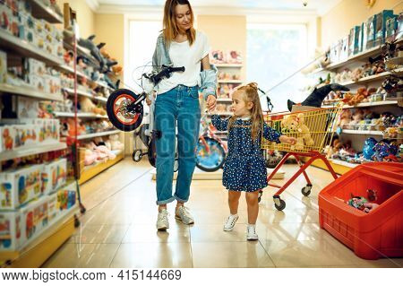 Mother and little girl buying bicycle, kid's store
