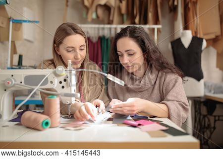 Two Femail Dressmakers Or Tailors Or Fashiondesigners Or Seamstresses Working With Sewing Machine At