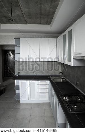 Modern Minimalism Style Kitchen Interior In Monochrome Tones. Custom Kitchen With Grey White Facades