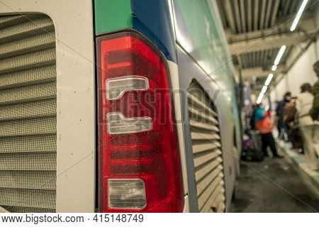 Selective Focus Of Rear Lights Of A Bus And Blurred Passengers Wait In A Line To Get In A Bus In Bus