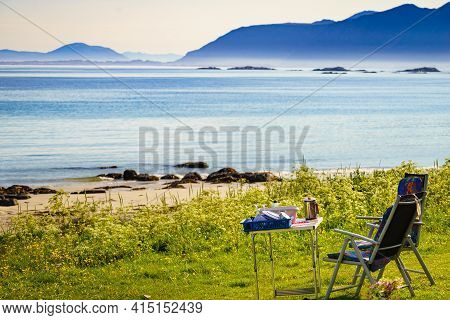 Camping Portable Chairs And Table With Kitchen Utensil On On Norwegian Fjord Shore. Holidays Relaxat