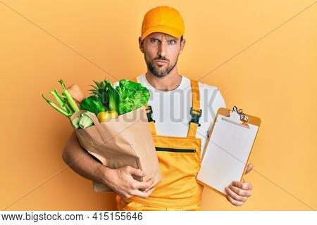 Young handsome man wearing courier uniform with groceries and clipboard skeptic and nervous, frowning upset because of problem. negative person.