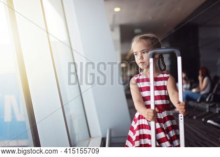 Young Passenger In Airport, Cute 7 Years Old Girl Looking At The Window On Planes In Terminal Hall W