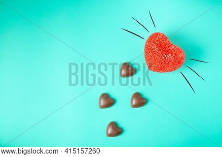 Chocolate Hearts Looks Like Cat Footprints On A Turquoise Background, Close-up. Concept. Chocolate C