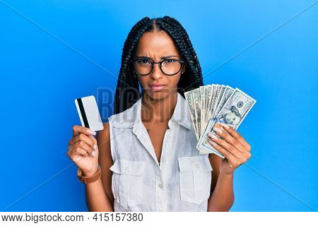 Beautiful hispanic woman holding dollars and credit card skeptic and nervous, frowning upset because of problem. negative person.