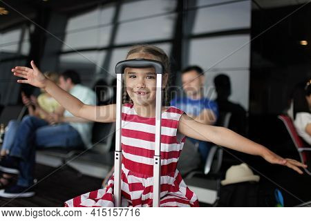 Young Passenger In Airport, Cute 7 Years Old Girl Sitting In Terminal Hall While Waiting For Her Fli