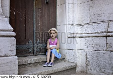 A Caucasian Girl In Summer Dress Is Sitting On Stone Stairs Before The Ancient Church, Outdoor Emoti