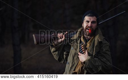 Bearded Man Hunter In A Warm Hat In A Long Green Cloak With A Gun On His Shoulder And A Large Backpa