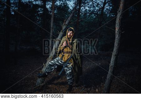 Serious Bearded Male Hunter In A Hat And A Long Green Cloak With A Hunting Rifle And Cartridges On H