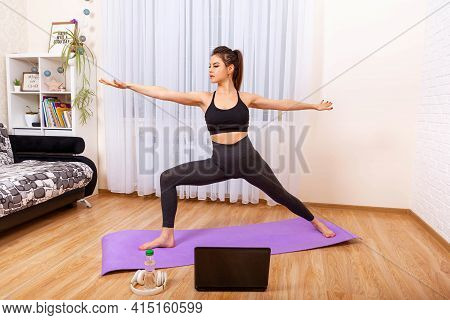 Girl Doing Yoga At Home. Yoga Online On The Laptop. Healthy Lifestyle. Fit Woman Doing Yoga And Watc