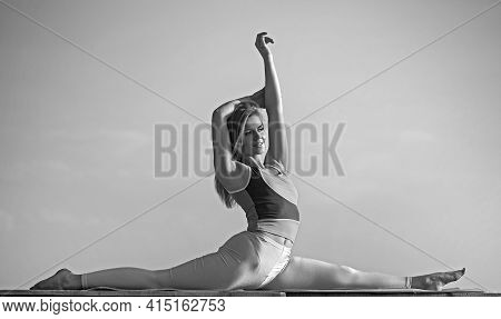 Beautiful Young Girl Doing Split Or Pilates Exercise Isolated On The Roof Against The Sky And Mounta