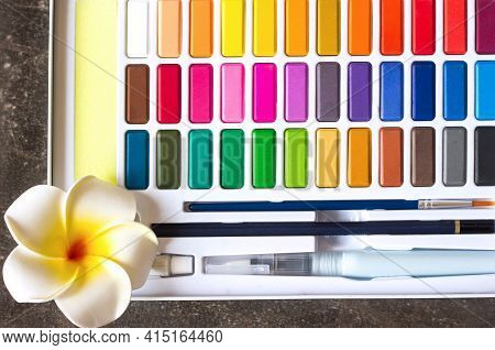 A Palette Of Bright Multicolored Watercolors, Brush And Pencil Close-up, Artist's Tools All Colors O