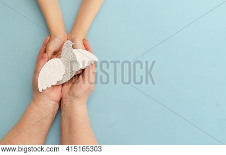 Hands Of Mother And Child Holding White Dove Bird On Blue Background. International Of Peace Or Worl