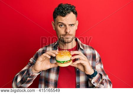 Young hispanic man eating a tasty classic burger skeptic and nervous, frowning upset because of problem. negative person.