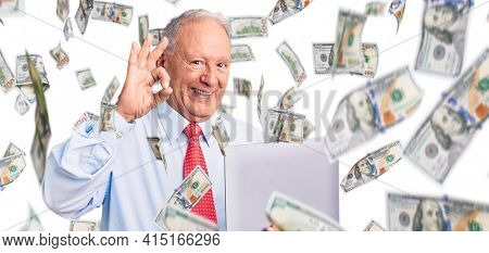 Senior handsome grey-haired man wearing tie using laptop doing ok sign with fingers, smiling friendly gesturing excellent symbol