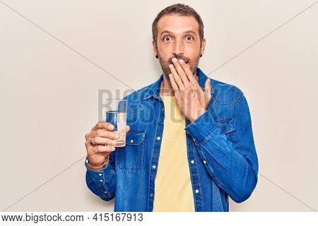 Young handsome man drinking glass of water covering mouth with hand, shocked and afraid for mistake. surprised expression
