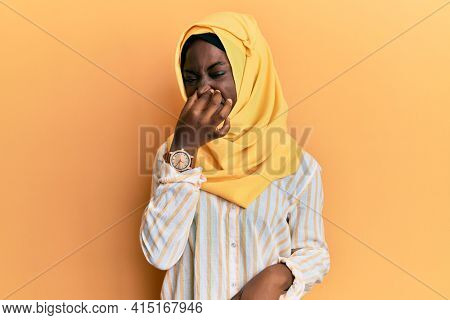 Beautiful african young woman wearing traditional islamic hijab scarf smelling something stinky and disgusting, intolerable smell, holding breath with fingers on nose. bad smell