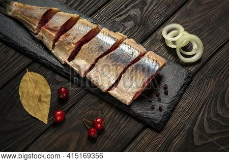 Dutch Raw Herring With Onions And Spices On A Serving Board. The Idea Of A Snack For A Street Cafe.