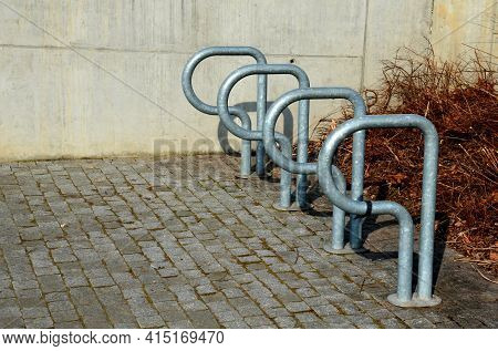 Parking Lot With Bicycle Stands Made Of Shiny Twisted Tubes For Inserting And Locking Bicycles In Th