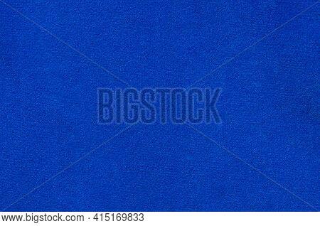 Uniform Texture Of Blue Felt Close-up. Blue Fabric Background Felt In Soft Light