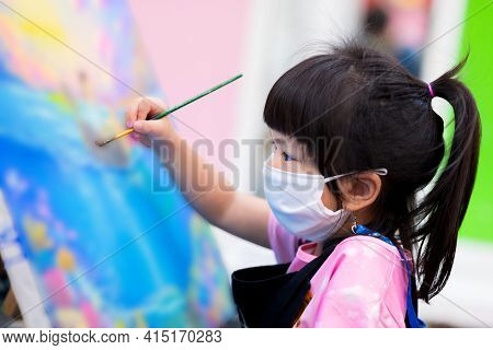 Pupil wear white cloth mask. Child work with watercolor art on canvas on easel. Kids holding paintbrush in right hand, makes craft with fun. Girl wear black apron to prevent color tracking of clothing