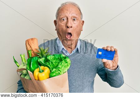 Senior caucasian man holding groceries and credit card afraid and shocked with surprise and amazed expression, fear and excited face.