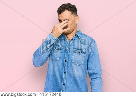 Young hispanic man wearing casual denim jacket smelling something stinky and disgusting, intolerable smell, holding breath with fingers on nose. bad smell
