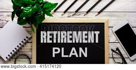 Retirement Plan Is Written In White On A Black Board Next To A Phone, Notepad, Glasses, Pencils And