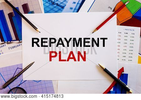 The Words Repayment Plan Is Written On A White Background Near Colored Graphs, Pens And Pencils. Bus