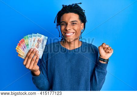 Young african american man holding swiss franc banknotes screaming proud, celebrating victory and success very excited with raised arm