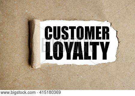 Customer Loyalty. Text On White Paper Over Torn Paper Background.