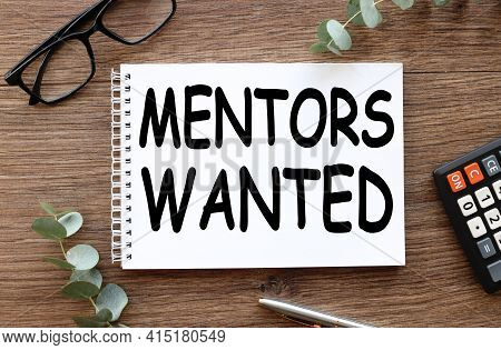 Mentors Wanted. Text On White Paper On Wood Table Background