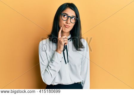 Beautiful asian young woman wearing business shirt thinking concentrated about doubt with finger on chin and looking up wondering